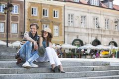 tourist couple sitting on steps against building - stock photo