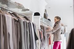 Stock Photo of side view of woman choosing sweater in store