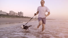 Happy man running dog on beach lifestyle steadicam shot Stock Footage