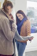 Stock Photo of female friends choosing sweater in store