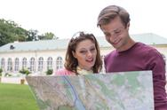 Stock Photo of young tourist couple with map against building