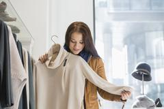 Stock Photo of young woman choosing sweater in store
