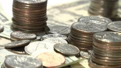 Stacks of coins and paper bills rotating on a turntable - stock footage