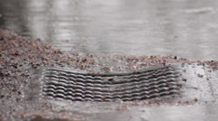 Rain falling on the street,water goes into manhole,close up shot Stock Footage