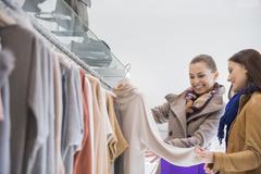 Stock Photo of happy friends choosing sweater in store