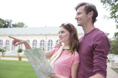 woman with map showing something to man against building - stock photo