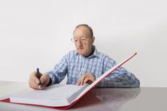 Stock Photo of senior businessman writing in file at desk