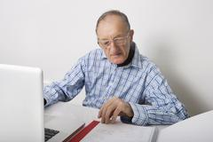 Stock Photo of senior businessman using laptop while reading file at office desk