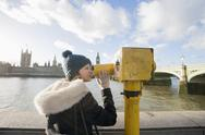 Stock Photo of side view of young woman looking through telescope by river thames; london; u