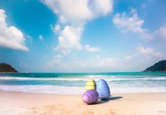 Three color Easter eggs on the sandy beach - stock illustration