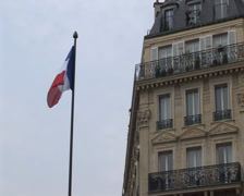 French flag, pan down to street scene in Paris, France Stock Footage