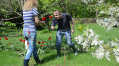Man husband pick tulip flowers give woman wife in spring garden Stock Footage