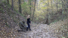 Woman leaves an angel wooden bench goes path covered leaves Stock Footage
