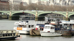 Boats on river thames red bus on bridge Stock Footage