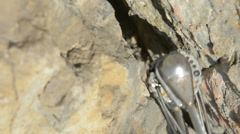 Rock climbing cam being placed in crack slow motion Stock Footage