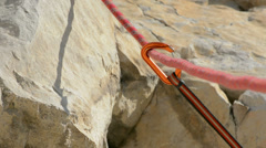 Climbing rope passing through carabiner slow pan right - stock footage