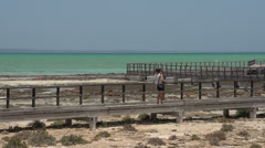 Pan from a girl walking at the pier from Modern stromatolites landscape Stock Footage