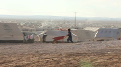 Child with a wheelbarrow in Zaatari Refugee Camp - stock footage