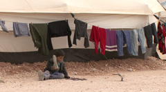 Child handling a shoe in Zaatari Refugee Camp Stock Footage