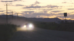 Headlights Shine As Car Approaches On An Empty Desert Dirt Road Stock Footage