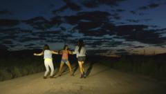 Friends Dance In The Headlights Of A Car, On A Desert Road Stock Footage