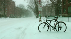 Lonely bike in snow storm, city street, no cars pass until mid clip Stock Footage