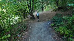 Woman hiking in deep forest -steadicam shot, rear view Stock Footage