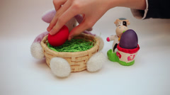 Hand putting Easter eggs in bunny basket decoration, cow egg holder, celebration - stock footage