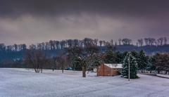 house and snow covered field in rural york county, pennsylvania. - stock photo