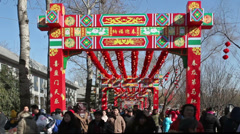 People walk under the decorated archway at temple fair Stock Footage