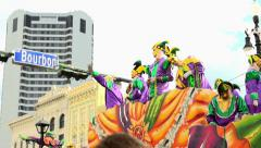 Mardi Gras float throwing beads passing Bourbon Street slow motion Stock Footage