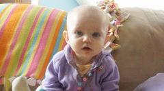 Baby nods and stares at camera Stock Footage