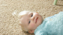 Toddler nods then begins to stand up from floor Stock Footage