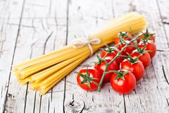 uncooked pasta and fresh tomatoes - stock photo