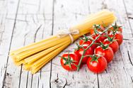 Stock Photo of uncooked pasta and fresh tomatoes