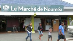 Local family walks past city market, noumea, new caledonia Stock Footage
