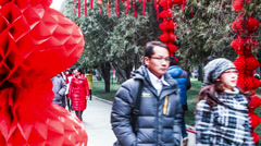 People walk under the red lanterns at Ditan Park Stock Footage