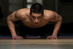 Young man exercising push ups Stock Photos