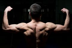 Young male athlete flexing back muscles Stock Photos