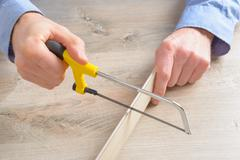 cutting plastic molding with handsaw - stock photo