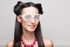 pin up model in heart shaped sunglasses. red polka shorts and bra - stock photo