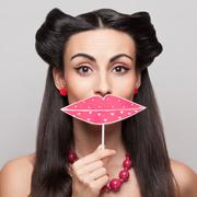 pinup girl holding big pink lips sign - stock photo