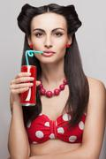 close-up of drinking soda beautiful model in pinup costume - stock photo