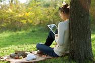 Stock Photo of distance education. sitting woman using ipad during stroll outdoors