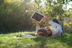 woman lying on bedding on green grass with ipad during picknic in the park - stock photo