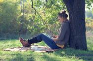 Stock Photo of hipster style young woman using tablet pc during a rest under the tree