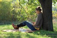Stock Photo of hipster girl leaning on a tree and using tablet computer