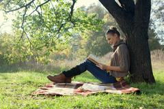 woman sitting on bedding on green grass with a book during picnic in the even - stock photo