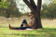 Stock Photo of hipster style young woman reading a book in autumn park during picknic