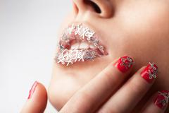 womans creative visage lips and manicure with scissors - stock photo
